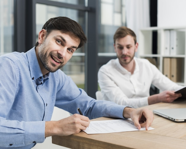 Side view of man signing work contract Free Photo
