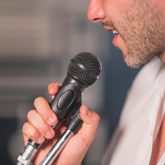 Вид сбоку человек поет в микрофон Бесплатные Фотографии