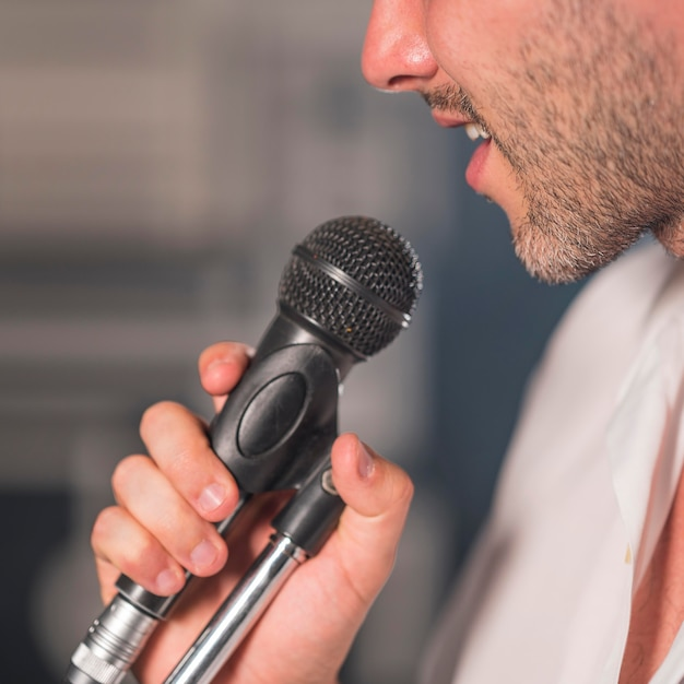 Side view man singing at microphone Free Photo