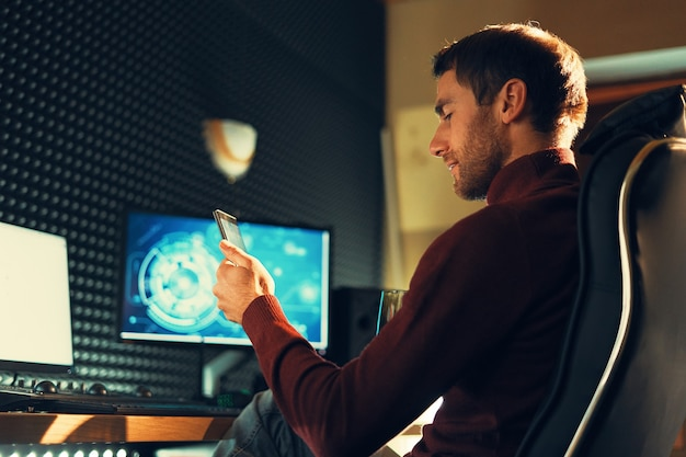 Вид сбоку человек, сидящий в кожаном кресле, работает в студии с помощью смартфона и компьютеров. фрилансер держит мобильный телефон, работая над кадрами, видео, дизайном. Premium Фотографии