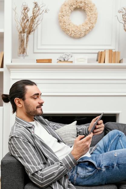 태블릿 소파에 앉아 측면보기 남자 프리미엄 사진