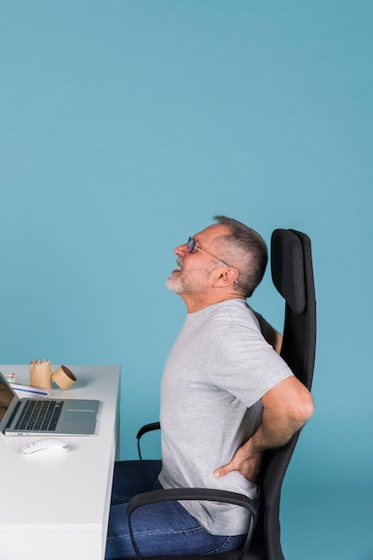 Side view of a man suffering from backpain while working on laptop Free Photo