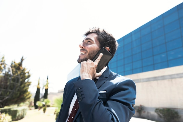 Side view man in suit talking on the phone Free Photo