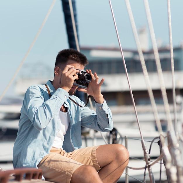 Вид сбоку человек фотографирует Premium Фотографии