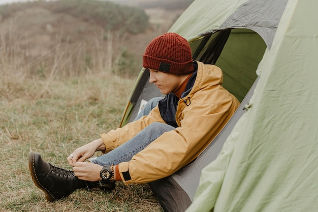 Side view man in tent binds laces Free Photo