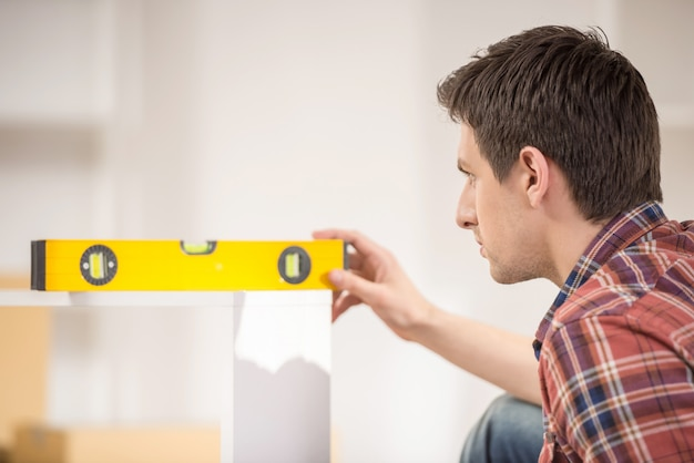 Side view of a man using spirit level at home. Premium Photo