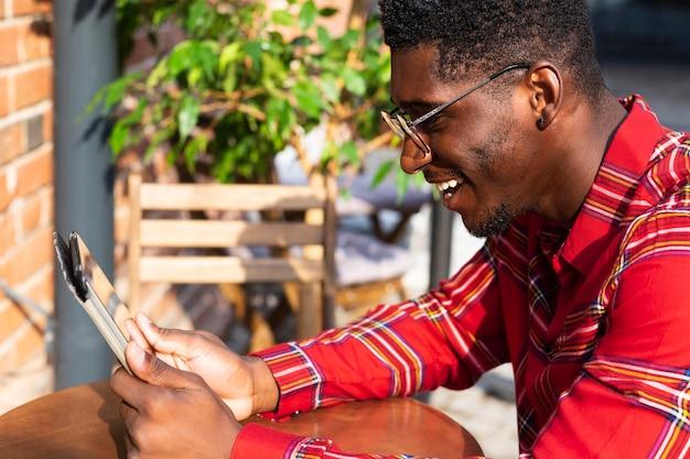 Uomo di vista laterale con gli occhiali e la lettura Foto Gratuite