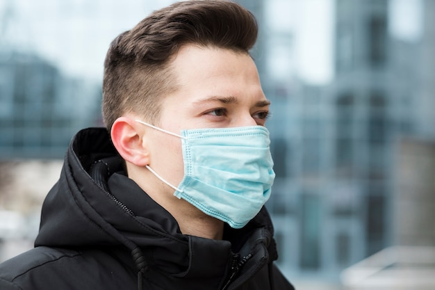 Side view of man wearing medical mask in the city Free Photo