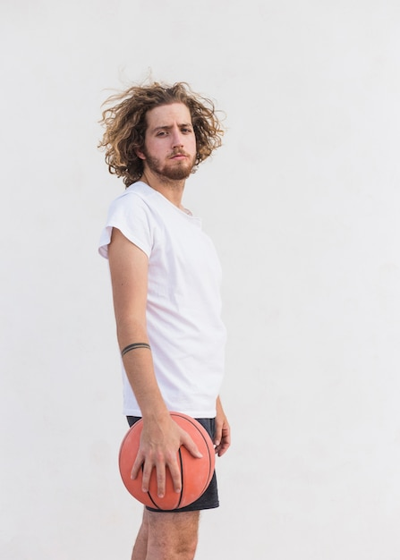 Side view of a man with basketball standing against white background Free Photo