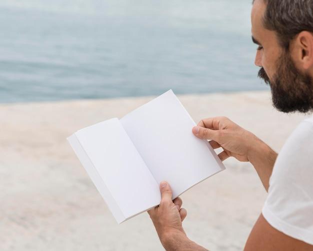 Vista laterale dell'uomo con la barba che legge all'aperto Foto Gratuite