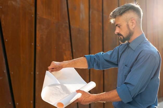 Side view of man with blueprint Free Photo