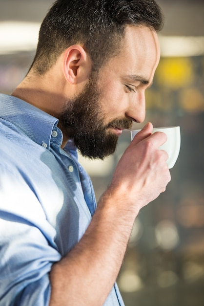 Side view of man with a cup of coffee through glass. Premium Photo