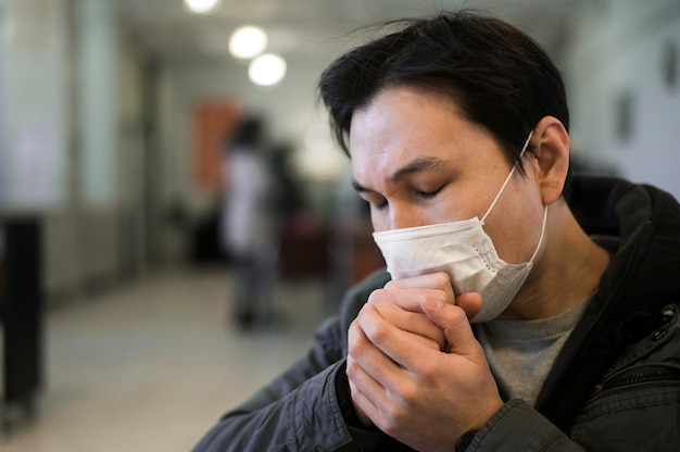 Side view of man with medical mask coughing Free Photo