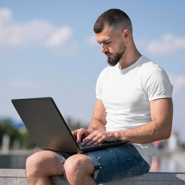 Вид сбоку человек, работающий на своем ноутбуке за пределами Бесплатные Фотографии