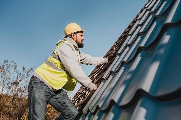 屋根に取り組んでいる側面図の男 Premium写真