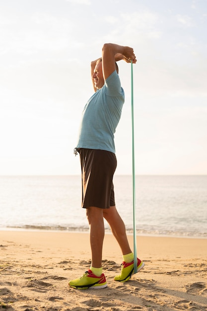 Side view of mature man working out with elastic rope on the beach Free Photo