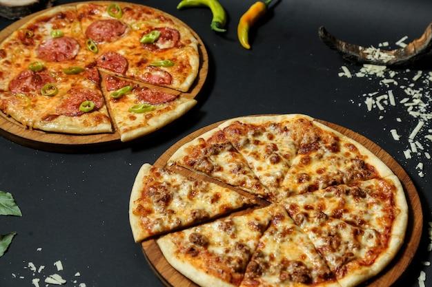 Вид сбоку мясная пицца на подносе с салями пиццей и острым перцем на черном столе Бесплатные Фотографии
