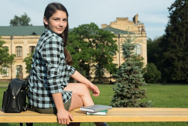 Side view medium shot of highschool girl sitting on bench Free Photo