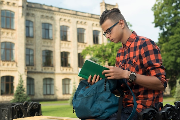 Side view medium shot teenage boy reading a book Free Photo
