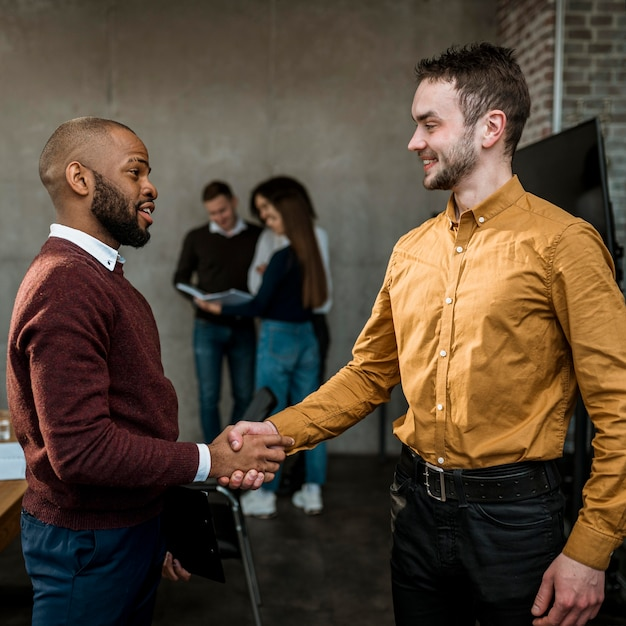 Side view of men handshaking in agreement after a meeting Free Photo