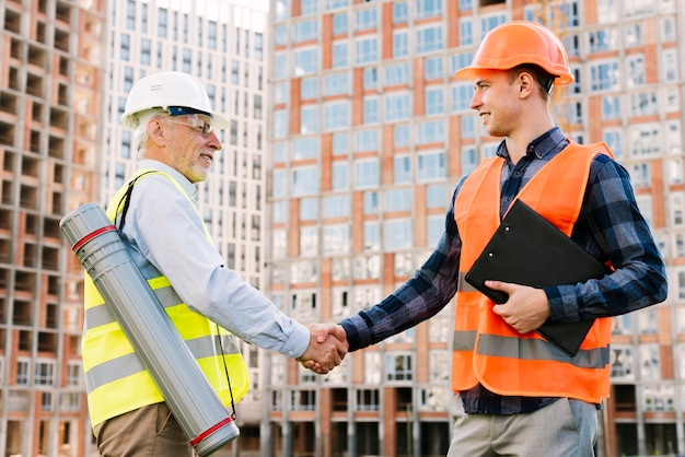 Side view men with safety vests shaking hands Free Photo
