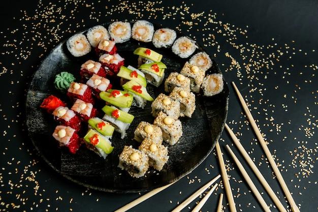 黒の背景にわさび生姜プレートとゴマと箸のロール寿司ロール 無料写真