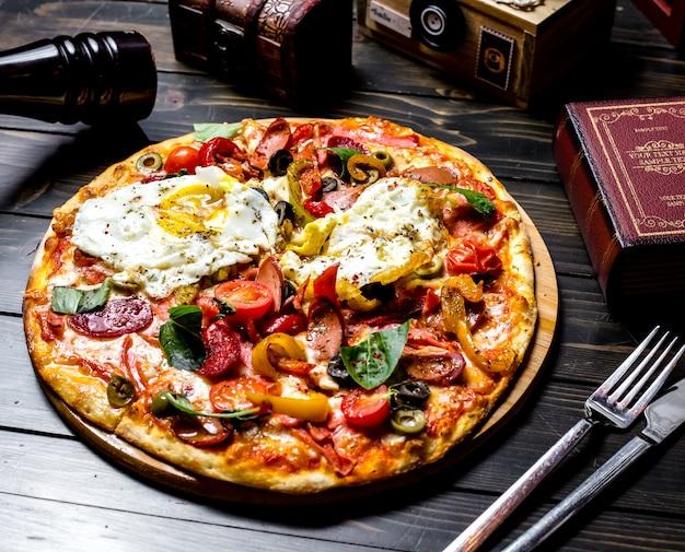 토마토 올리브 피망 계란 소시지 보드에 책과 나이프와 포크 테이블에 측면보기 혼합 피자 무료 사진