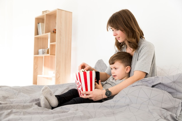 Side view mom and son eating popcorn Free Photo