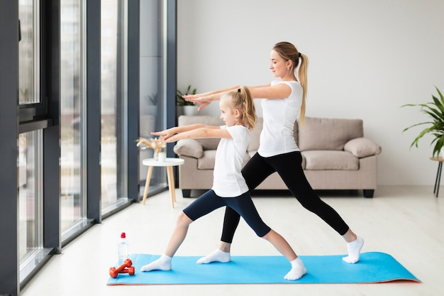 Side view of mother exercising along with child at home Free Photo