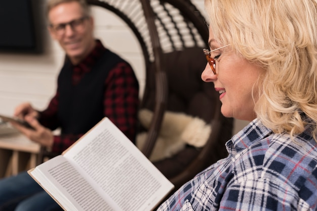 Side view of mother reading book with defocused father Free Photo