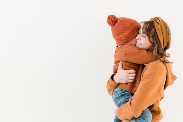 Вид сбоку мать с сыном на руках Бесплатные Фотографии