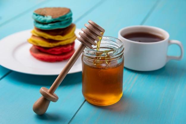 Vista laterale frittelle multicolori su una piastra con miele in un barattolo e un cucchiaio di miele in legno con una tazza di tè su uno sfondo turchese Foto Gratuite