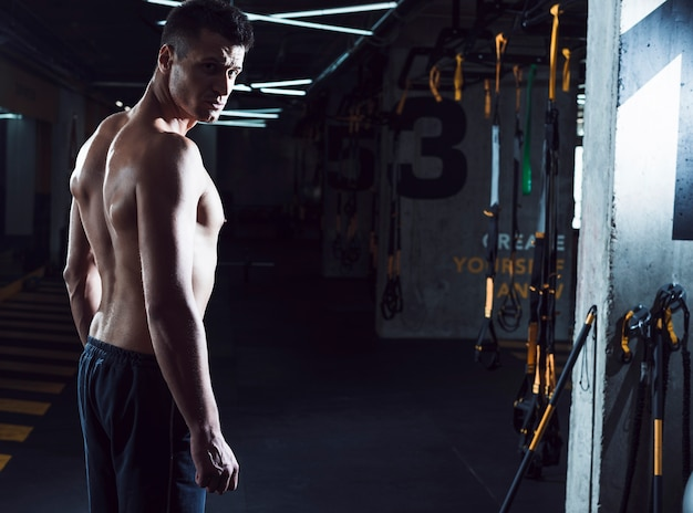 Side view of a muscular young man standing in fitness club Free Photo