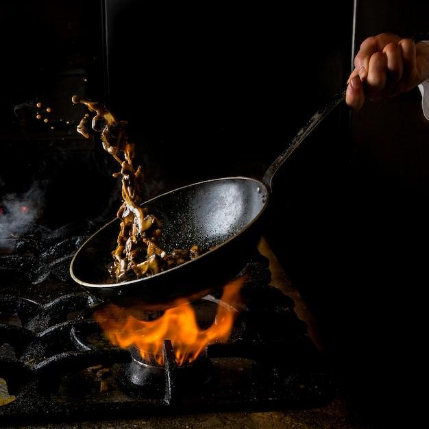 Вид сбоку гриб жарки с газовой плитой и огнем и человеческой рукой в кастрюле Бесплатные Фотографии