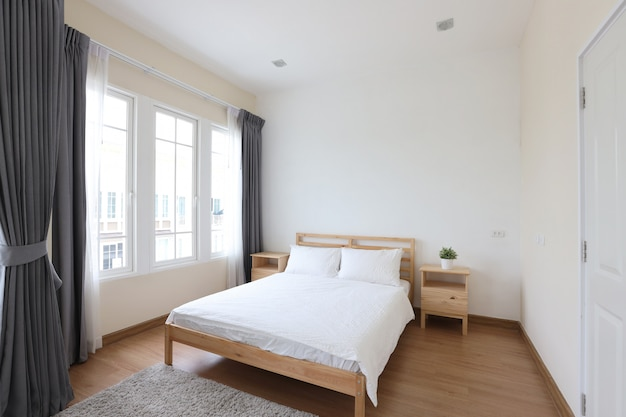 Side view of new modern white wooden bed in white bedroom with soft and clear light Premium Photo