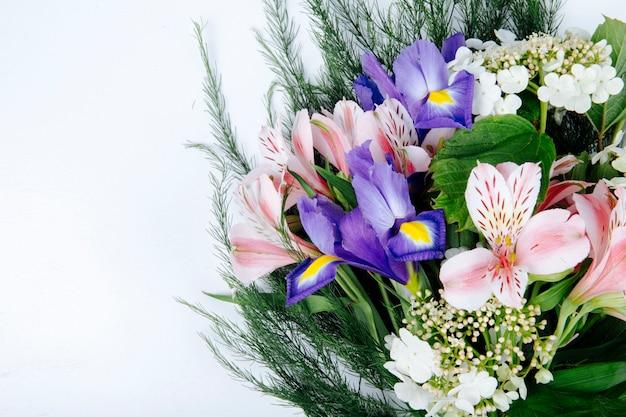 白地に濃い紫色のアイリス咲くガマズミ属の木とアスパラガスとピンク色のアルストロメリアの花の花束の側面図 無料写真