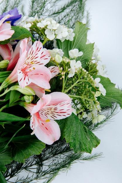 白地に暗い紫色のアイリス咲くガマズミ属の木とピンク色のアルストロメリアの花の花束の側面図 無料写真