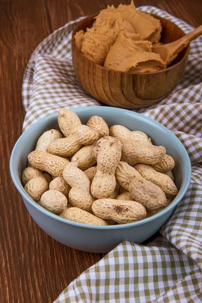 Вид сбоку миску с арахисом в скорлупе с арахисовым маслом в деревянной миске на клетчатой скатерти Бесплатные Фотографии