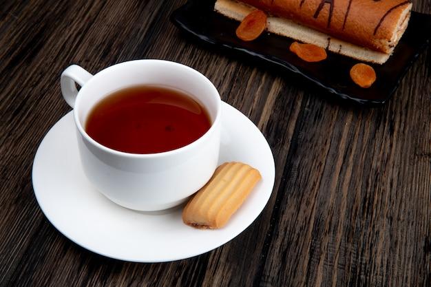 Чашка чая с печеньем и рулет на подносе на деревенской деревянной поверхности, вид сбоку Бесплатные Фотографии