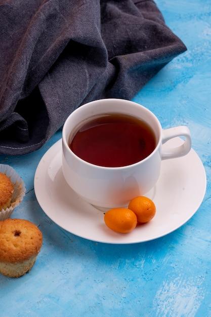青いテーブルにおいしいマフィンとお茶のカップの側面図 無料写真