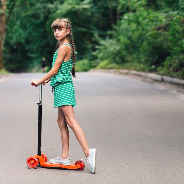 Side view of a girl standing over the scooter on road Free Photo