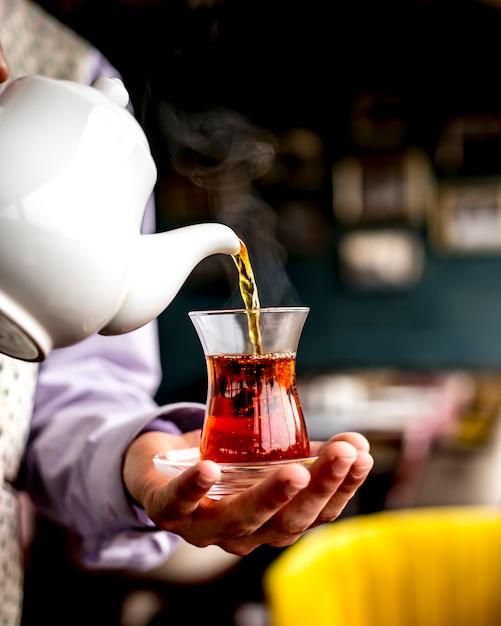Вид сбоку человека, наливающего черный чай из белого керамического чайника в стакан armudu Бесплатные Фотографии