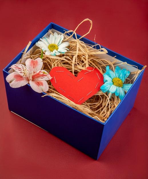 赤いテーブルに紙とデイジーとアルストロメリアの花から作られたわら、赤いハートで満たされたプレゼントボックスの側面図 無料写真