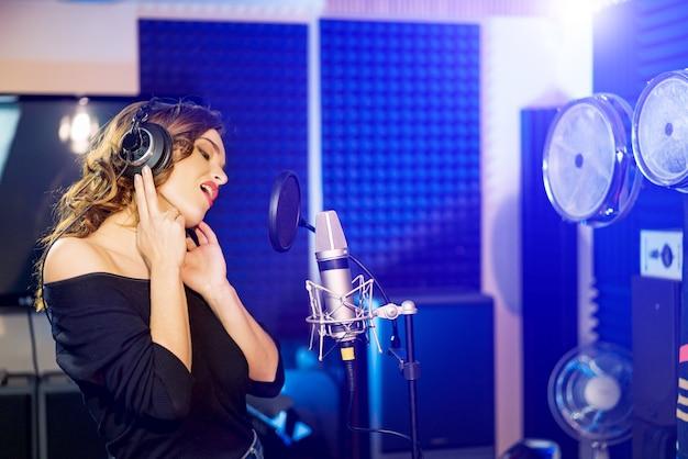 Взгляд со стороны милой женщины стоя в студии с наушниками и поя перед микрофоном. Premium Фотографии