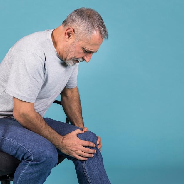 Вид сбоку старшего человека с болью в колене, сидя на стуле Premium Фотографии