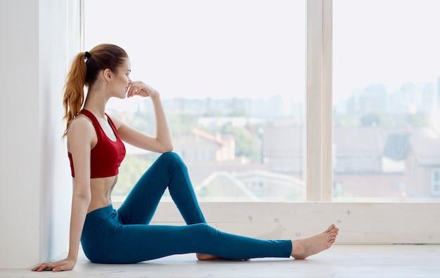 창턱과 빨간 티셔츠 요가 피트니스에 앉아 파란색 레깅스에 여자의 측면보기. 프리미엄 사진