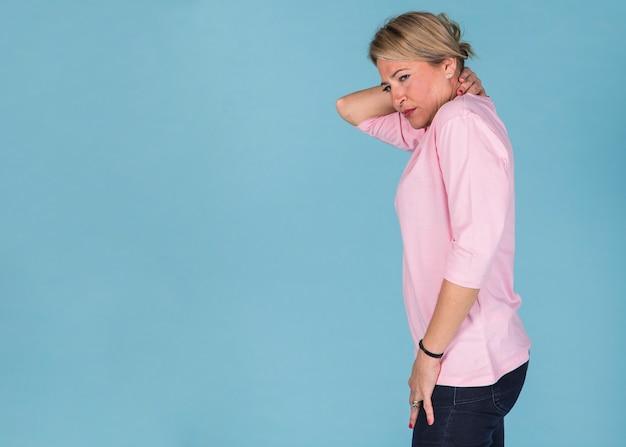 Вид сбоку женщины, страдающей от боли в шее на фоне синих обоев Бесплатные Фотографии