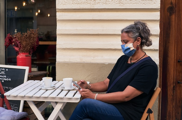 カフェの屋外テーブルで彼女の携帯電話を使用しながらフェイスマスクを持つ女性の側面図 無料写真