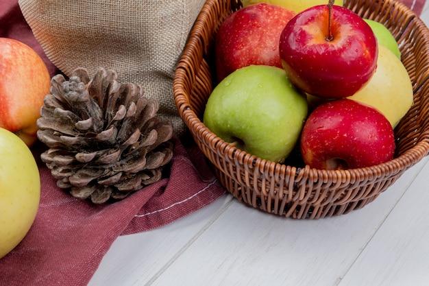 Вид сбоку яблок в корзине с шишкой и яблоками на ткани бордо и деревянной поверхности Бесплатные Фотографии