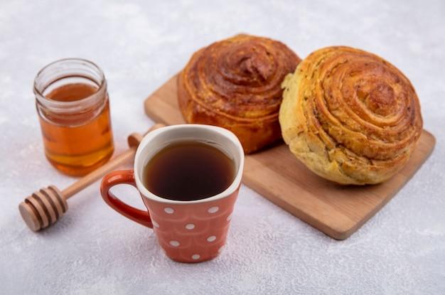 白い背景の上のガラスの瓶にお茶と蜂蜜のカップと木製のキッチンボード上のアゼルバイジャンの伝統的なペストリーgogalの側面図 無料写真